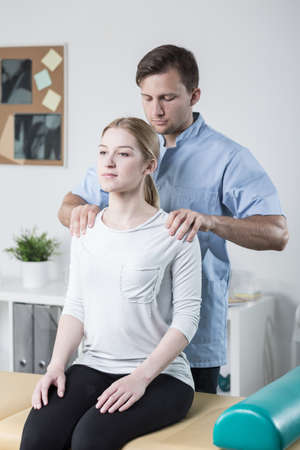 examining: Male physiotherapist examining womans back and shoulders Stock Photo