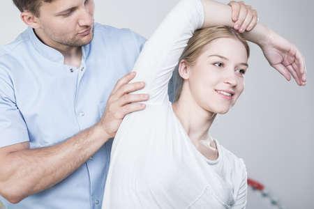 젊은 물리 치료사 재활하는 동안 여자의 팔을 스트레칭