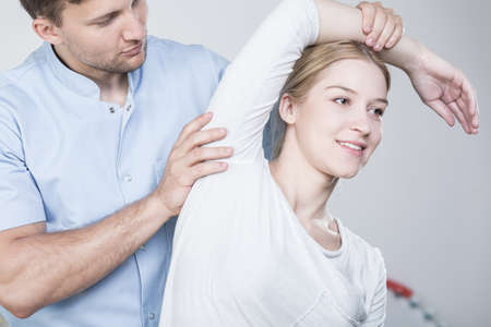 Jonge fysiotherapeut die zich uitstrekt van de vrouw arm tijdens de revalidatie