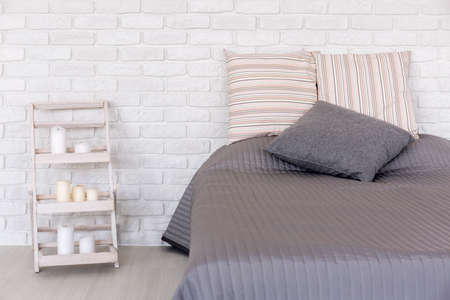 scandinavian: White bedroom with decorative brick wall, large bed and handmade nightstand Stock Photo