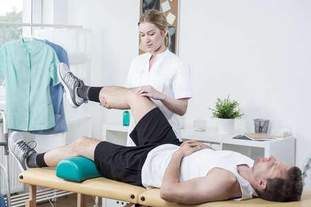 lower limb: Horizontal view of female chiropractor exercising mans leg Stock Photo
