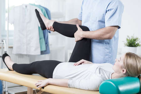 lower limb: Male chiropractor stretching female leg during rehabilitation Stock Photo