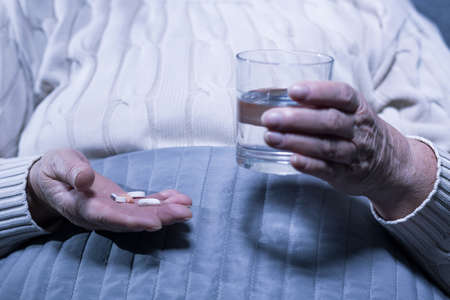 cropped out: Cropped picture of an old woman holding out some pills and a glass of water