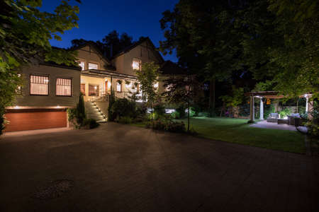 Photo of new white mansion with large cobbled driveway
