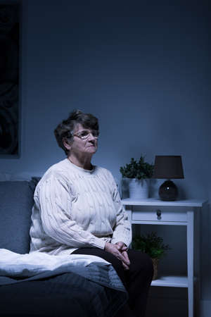 solitude: Shot of an old woman sitting alone in a room at night Stock Photo