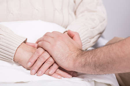people problems: Cropped picture of two people holding hands