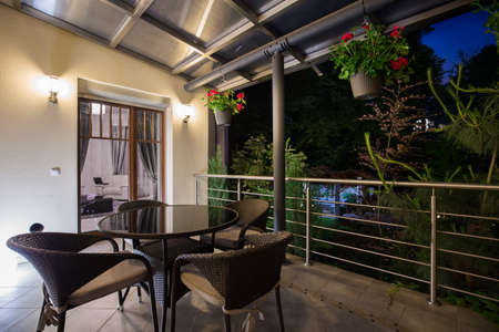 Picture of covered terrace with elegant furniture at night
