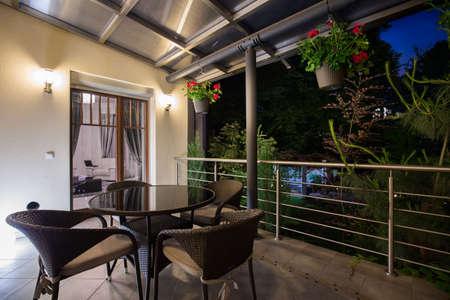 Foto van overdekt terras met elegant meubilair in de nacht