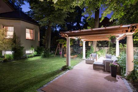 夜の屋根付きのパティオと庭園の写真