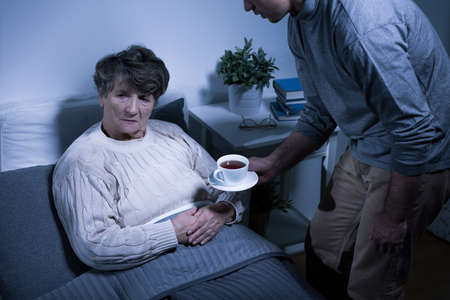 refusing: Shot of an senior woman refusing to take a cup of tea from her grandson