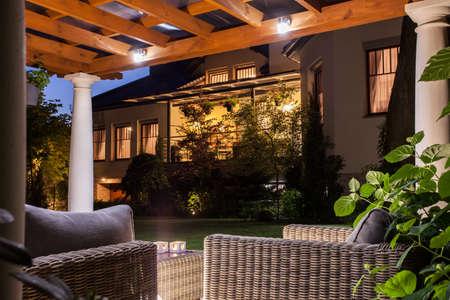 Zdjęcie pięknej rezydencji z ogrodem w nocy