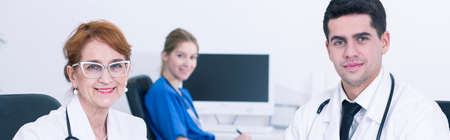ambulatory: Panorama of two doctors, a young and an older one, smiling at the camera, with a young doctor sitting in the background Stock Photo