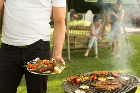 Man holding plate full of grilled food Stock Photo