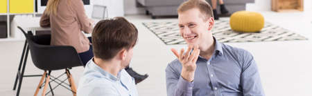 workmate: Panorama of two colleagues in a modern office, smiling and talking in a relaxed pose Stock Photo