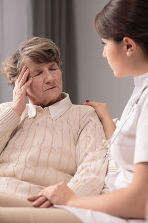 terrible: Elderly woman with terrible headache and supportive nurse