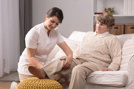 carer: Older woman with painful knee and helpful carer