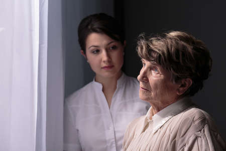 Sad older woman in nursing home waiting for relatives