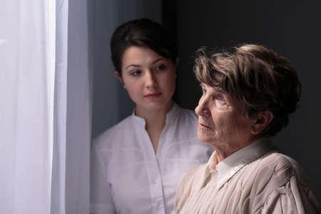 pielęgniarki: Sad starsza kobieta w domu opieki czekają na krewnych