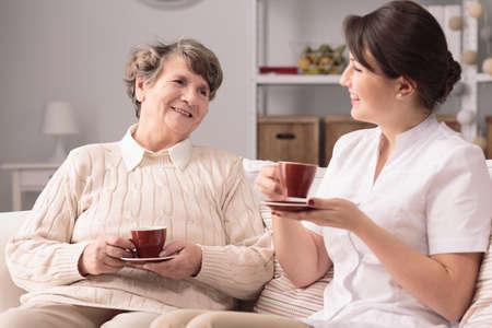 ancianos felices: joven enfermera servicial y amable sala sonriendo