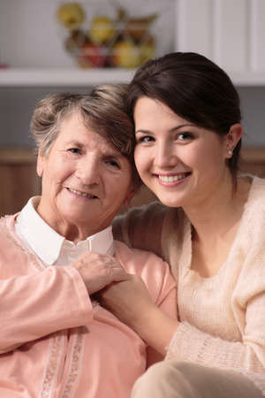 Young pretty caregiver and older happy patient together