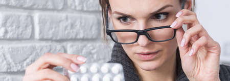 abuser: Close-up of smart young woman in glasses checking drugs composition before using