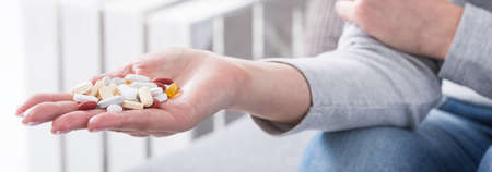 Close-up of girl holding handful full of colorful pills. Woman addicted to medicine