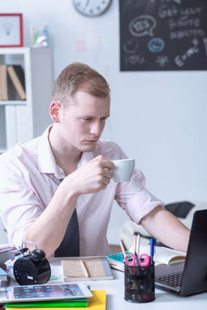 hombre tomando cafe: Shot of a focused young man drinking coffee and using his laptop