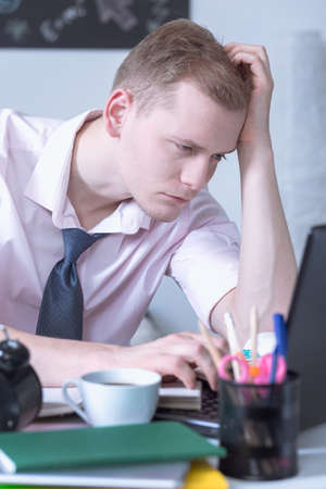 bored student: Shot of a young bored student using his laptop to study Stock Photo
