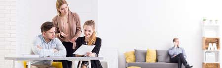 Panorama d'un bureau moderne et minimaliste avec l'équipe de collègues discuter des documents à un bureau blanc et un jeune homme parlant au téléphone en arrière-plan