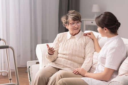 Piuttosto giovane badante parlare con pazienti anziani