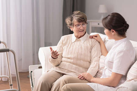 talk: Young pretty caregiver talking with older patient