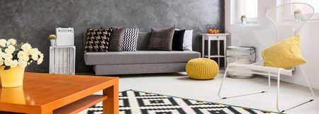 #55290958   Panorama Von Einem Wohnzimmer In Grau Ausgestattet Und Weiß,  Mit Einem Hölzernen Couchtisch Mit Blumen Im Vordergrund Dekoriert