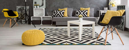 Panorama of a spacious modern living room arranged in scandinavian style, furnished in grey and white with yellow elements Stock Photo