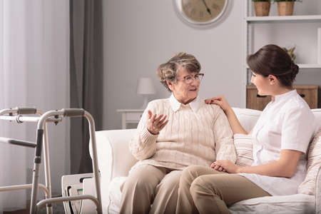 Supportive young carer sitting with older patient Stock Photo