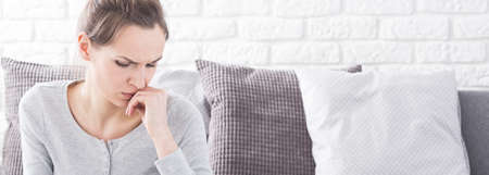 abuser: Young pretty woman with pain worried about her health. Sitting alone on a couch in room Stock Photo