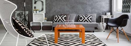 Panorama van een minimalistische lounge, ingericht in zwart en wit met draad stoel in de voorgrond en draad kom staande op een houten salontafel
