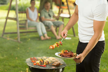 barbeque: Close-up of host serving delicious grilled meal