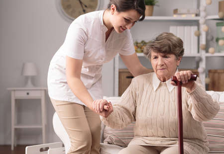 carers: Senior disabled woman standing up with carers help
