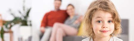 In einem Hintergrund-Bild von einem entzückenden kleinen Mädchen und ihre Eltern sitzen auf einem Sofa Standard-Bild - 55291109