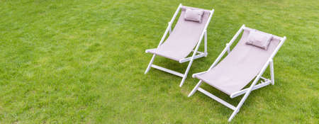 deck chairs: Two white deck chairs in the garden Stock Photo