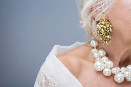 Primer plano de cuello alto de la mujer elegante con los collares de Perl y el oído con el pendiente de oro Foto de archivo