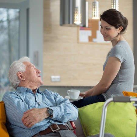 in loved: Grandfather talking with loved granddaughter in his home