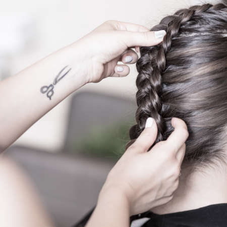 woman hairstyle: Professional hairdresser creating a braided hairstyle to her client Stock Photo