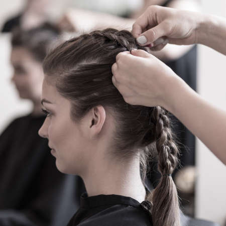 braiding: Female hairdresser is braiding young womans hair