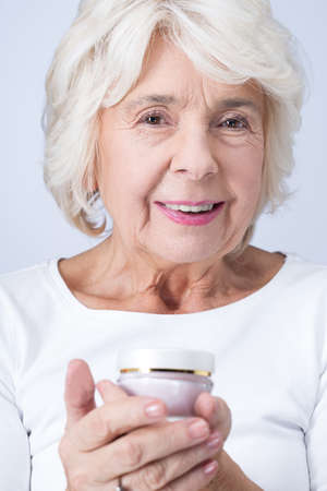 antiaging: Elderly pretty happy woman holding anti-aging cream in her hands