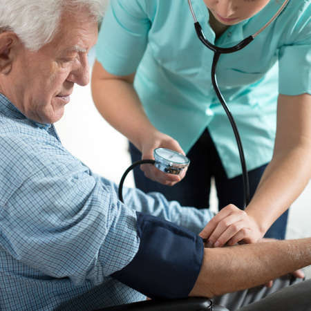 blood: Young attractive nurse checking the elderly mans hypertension Stock Photo