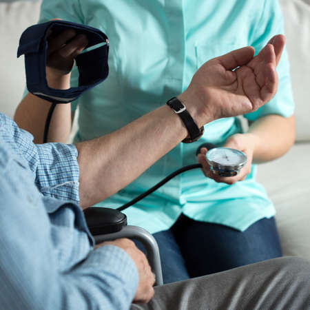 care home: Close-up of nurse measuring blood pressure disabled man