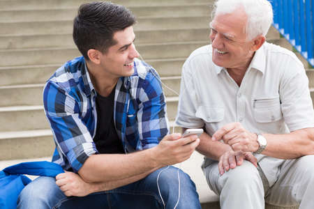 pensionary: Smiling young man talking with his grandfather Stock Photo