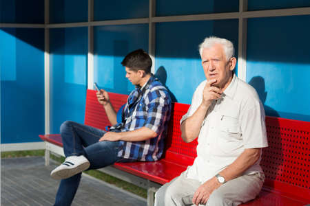 Men sitting on bench and waiting for bus 写真素材