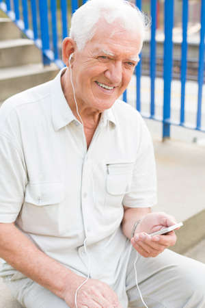 pensionary: Elderly smiling man is listening to music Stock Photo